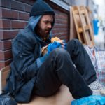 Bearded beggar eats burger on city street