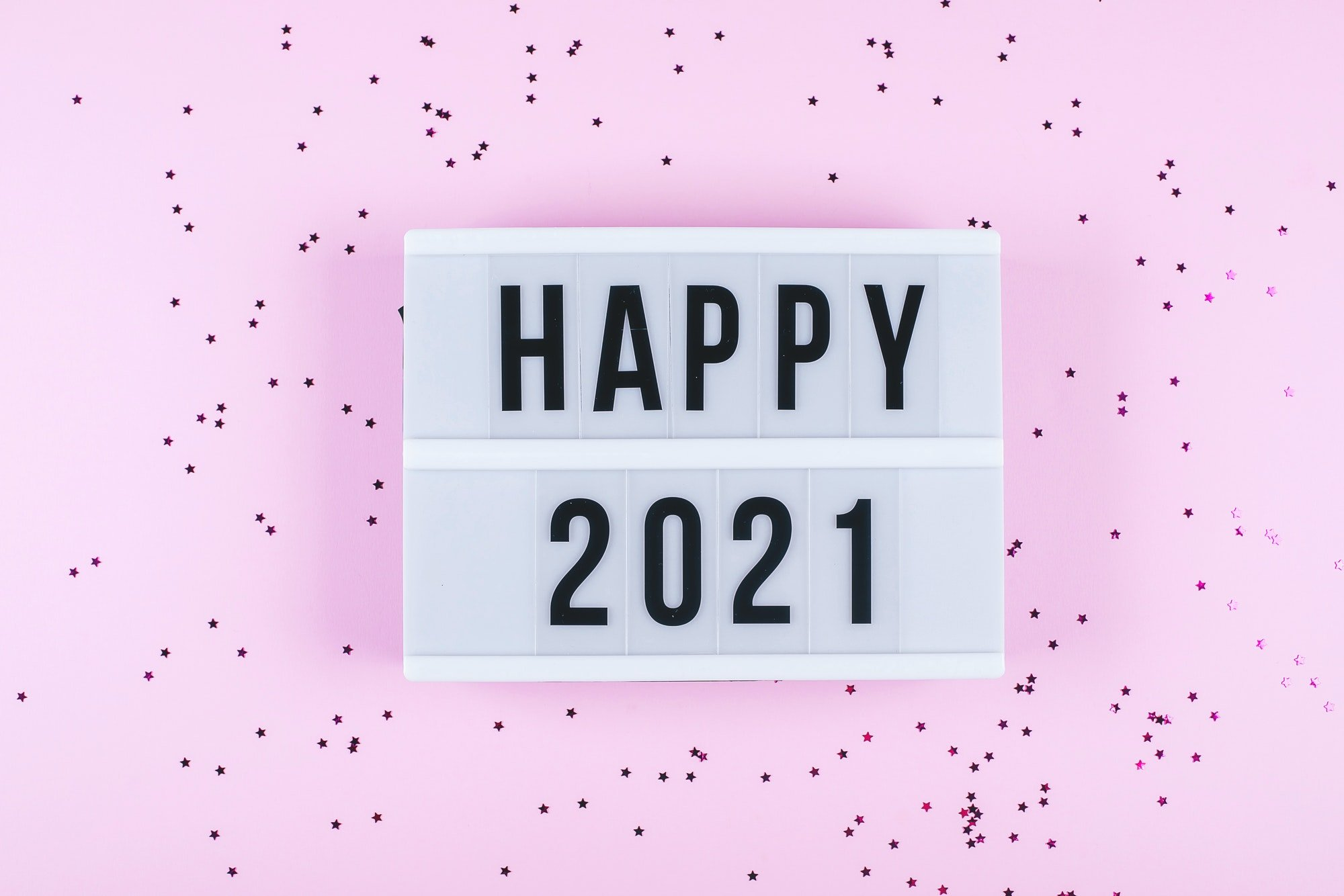 Happy New Year 2021 celebration. Light box with text Happy 2021 and sparkles on pink background