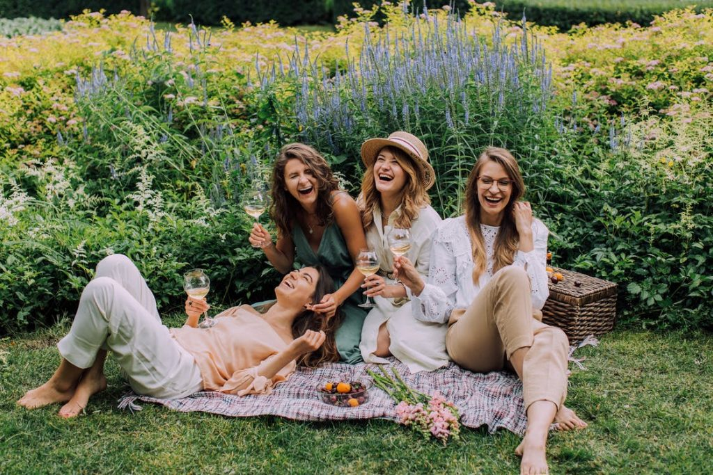 Four women laughing happily while in front of a lavender garden